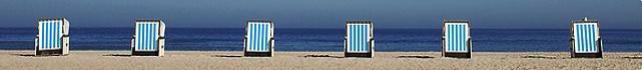 Blau-weiss-gestreifte Strandliegen am Meer
